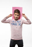 The artistic teenager boy brunette in a pink jumper with a pink sheet of paper for notes. On a white background Royalty Free Stock Images