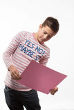 The artistic teenager boy brunette in a pink jumper with a pink sheet of paper for notes. On a white background Stock Photography