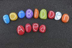 Forbidden area text composed with multi colored stones over black volcanic sand. Artistic text, Forbidden area, composed with multi colored sea stones over royalty free stock photos