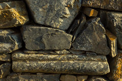 Artistic texture of a rustic vintage brownish stone wall to be u Royalty Free Stock Photos