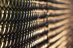 Artistic view of black chain link fence in evening sunlight Stock Photo