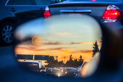 An artistic view of the busy traffic via side mirror at sunset in Los Angeles. Blurred road, headlights and rear lights. Of other cars royalty free stock image