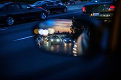 An artistic view of the busy traffic via side mirror at sunset in Los Angeles. Blurred road, headlights and rear lights. Of other cars stock photography