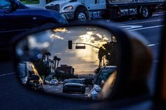 An artistic view of the busy traffic via side mirror at sunset in Los Angeles. Blurred road, headlights and rear lights stock photography