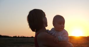 Beautiful woman with a child enjoying the sparkling rustic view at sunset stock photo