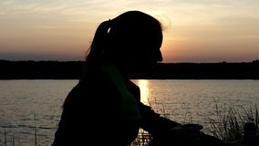 Young woman sits on a lake bank drinks tea from a thermos. An artistic view of a young woman who sits on a lake bank with a sun path on its surface and drinks stock footage