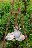 Vintage painters easel, paintbrushes and old wooden palette Stock Photography