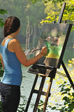 Artistic woman painting acrylic on canvas outside Royalty Free Stock Photos