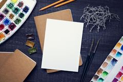 Artistic workplace mock up. With watercolor paper and painting supplies Stock Image