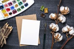 Artistic workplace mock up. With watercolor paper and painting supplies Stock Photos