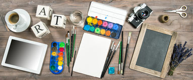 Artistic workplace mockup. Watercolor, brushes, digital tablet, Royalty Free Stock Photos
