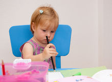 Artistic young girl. Cute preschool girl drawing on artwork table, white background Royalty Free Stock Photos