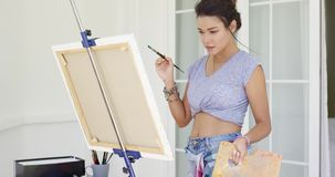 Artistic young woman working on a painting stock footage