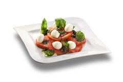 Artistically arranged tomato salad with mozzarella garnished wit Royalty Free Stock Image