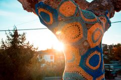 Artistically decorated tree with coloured wool, tree with storm. Yarn. Street Art. With the background sun stock images