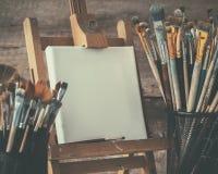 Artistiek materiaal: kunstenaarscanvas op schildersezel en verfborstels Stock Afbeelding