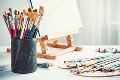 Artistiek materiaal: schildersezel, borstels, verven en leeg canvas stock foto's