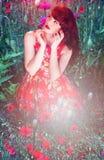 Artistiek portret van een vrouw onder rode papavers stock foto