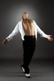 Artistieke mens die in studio, op grijze achtergrond dansen Stock Afbeelding