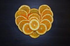 Artistieke samenstelling van plakken van rijpe die sinaasappelen in een vorm van een hart op houten achtergrond wordt gesteld royalty-vrije stock foto's
