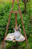 Artistieke uitstekende schildersezel, penselen en oud houten palet stock fotografie