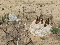Yard art, chairs and bottles. Artistry in the desert, chairs around a rock royalty free stock photos