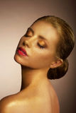 Artistry. Fanciful Bronzed Woman's Face. Futuristic Art Gold Makeup Stock Photography