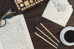 Artistry of letters writing. Wooden desktop with written notes, pencils and open letter envelope on Royalty Free Stock Photography