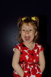 Artistry of a little girl on a black background close-up. Emotional child poses a face stock photo