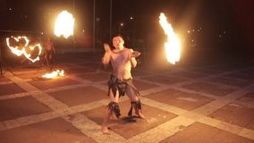 Artists in ancient dress demonstrate fire show during rain. stock footage