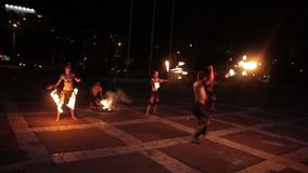 Artists in ancient dress demonstrate fire show during rain. stock video