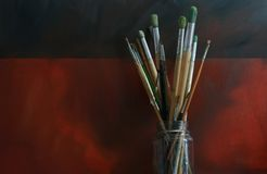 Artists Brushes. A pot of artists paint brushes set against an oil painted 'Grunge' styled canvas background. Copy space available stock image