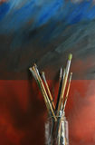 Artists Brushes. A collection of artists bushes in a glass jar set against a gunge styled oil on canvas painting Stock Photos