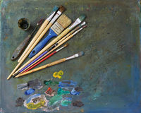 Artists brushes and oil paints. Palette with paintbrush and palette-knife Royalty Free Stock Images