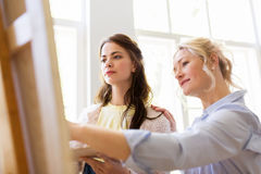 Artists discussing painting on easel at art school. Creativity, education and people concept - artists or student girl with palette and teacher discussing Stock Images