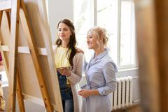 Artists discussing painting on easel at art school. Creativity, education and people concept - artists or student girl with palette and teacher discussing Royalty Free Stock Image