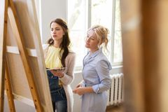Artists discussing painting on easel at art school Royalty Free Stock Photo
