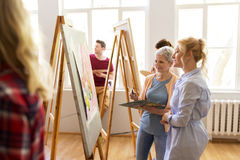 Artists discussing painting on easel at art school. Creativity, education and people concept - women artists discussing painting on easel at art school studio Royalty Free Stock Images