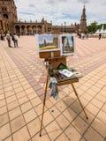Artists easel and artwork. Seville, Spain - May 20, 2014: Artists easel and artwork set up on the Spain Square Plaza de Espana, Seville, Spain Stock Image