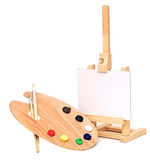 Artists easel. Photo of an artists easel with a blank canvas plus palette of paint and brushes, isolated on a white background Royalty Free Stock Photos