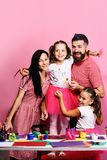 Artists family hugs on pink background. Creativity and family concept. Girls, men and women with happy smiling faces by their art desk. Parents and children stock image