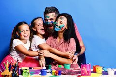 Artists family hugs and smiles. Girls, man and woman. Artists family hugs and smiles. Girls, men and women with cheerful faces by desk with paints. Parents and stock photos