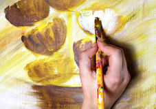 Artists hand with paintbrush painting the picture Stock Image