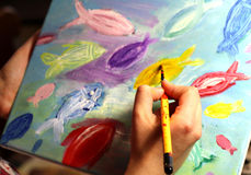 Artists hand with paintbrush painting the picture Royalty Free Stock Photos