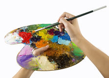 Artists hands holding a paint brush and palette Stock Image