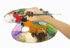 Artists hands holding a paint brush and palette Stock Photo