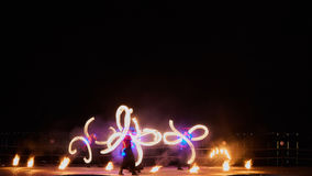 Artists juggling with burning poi's at fire performance. Royalty Free Stock Photography