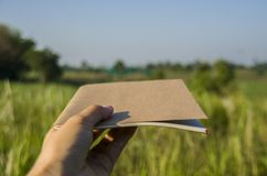 Hand hold on the brown notebook with natural light in garden outdoor at Chiang Ma,Thailand. royalty free stock image