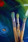 Artists paint brushes. Close up detail of a set of artisist brushes with a soft focus abstract coloured painting in the background, painted by myself as the Royalty Free Stock Photo