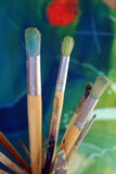 Artists paint brushes. Close up detail of a set of artisist brushes with a soft focus abstract coloured painting in the background, painted by myself as the Stock Photo